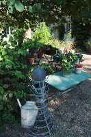 Watering can hanging on old bottle rack next to garden table on gravel floor