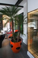 Lounge area with potted palms in orange pot and illuminated artwork on wall in retro interior