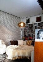 Extravagant round bed with fur blankets against white brick wall and shelves of records