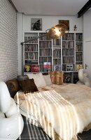 Extravagant round bed with fur blankets and retro standard lamp in front of white fitted shelves