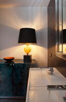 White designer twin washstand and artistic table lamp with black lampshade on elegant sideboard