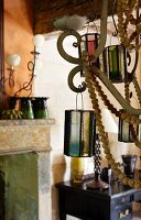 Detail of candle chandelier decorated with wooden beads and glass lanterns in vintage interior