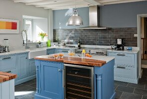 Country-house kitchen with pale blue fronts, central island with marble and walnut worksurfaces and integrated wine rack