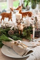 Linen napkin decorated with sprig of pine and silver bauble on plate on festive dining table