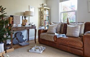 Scatter cushions on brown leather sofa below window and gifts on console table next to Christmas tree
