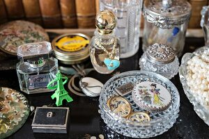 Vintage-style arrangement of perfume bottles and crystal dish of antique jewellery