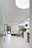 Open-plan interior with white floor and skylight