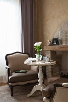 Vase of white tulips on round vintage side table and elegant armchair next to fireplace