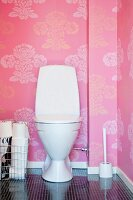 Toilet against pink wallpaper with floral pattern