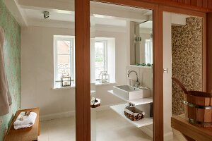 Washstand with shelves in modern bathroom seen through open glass door
