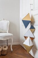 Geometric paper shapes hung from wardrobe door
