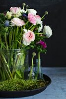 Arrangement of pink ranunculus and anemones in glass vases amongst moss on tray