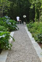 Gravel path with stone edging leading to vintage garden chair and watering can in front of green hedge