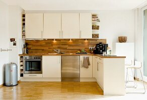Modern open-plan kitchen with pale cabinets and wooden worksurface