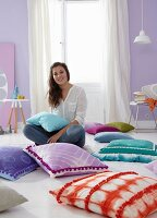 A woman sitting on the floor between cushions with brightly coloured covers