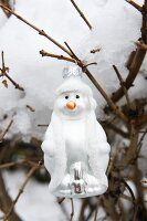 Snowman bauble hung from snow-covered branch in garden