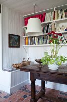Flowering potted plant on antique console table below bookshelves on white wooden wall
