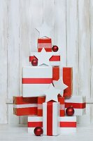 Gifts wrapped in red and white stacked in shape of Christmas tree