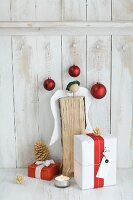 Gifts wrapped in red and white, baubles and angel made from log against board wall