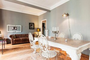 White metal chairs around dining table in front of brown leather couch in room with walls painted light grey