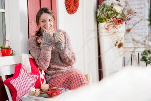 Smiling, young woman drinking coffee on wintry veranda