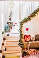Staircase festively decorated with garland, pine cones and lanterns