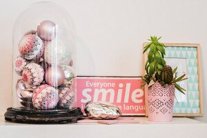 Various pastel Christmas baubles with crocheted covers under vintage glass cover next to pink enamel sign and plant on surface