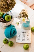 Christmas arrangement of green apples, turquoise felt flower, hellebore flowers and drawing on piece of wood on table