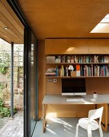 Computer on desk in modern extension with wood cladding, skylight and open terrace doors