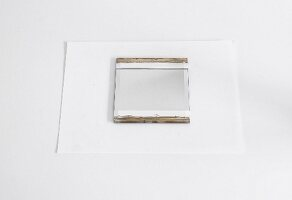 Mirror with areas masked with white masking tape and painted stripes