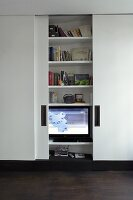 TV and bookcase behind simple, white, sliding doors