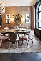 Upholstered chairs, oval dining table and framed photos flanking sunburst mirror in elegant dining room