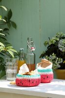 Crocheted watermelon baskets of biscuits next to glasses and swing-top bottles on garden table