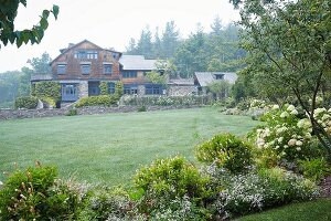 A spacious garden with a large lawn with an old arts-adn-crafts shingle house