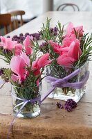 Romantic arrangements of cyclamen and sprigs of rosemary arranged in glass vases