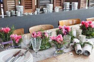 Romantic arrangements of cyclamen and sprigs of rosemary arranged in glass vases and in wreaths
