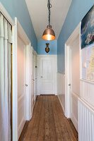 Narrow hallway with rustic wooden floor, white interior doors and blue-painted walls