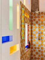 Vintage-style shower fitting on ornate wall tiles and stained-glass niches