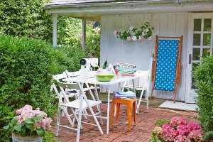 A sewing machine and sewing utensils on a table with folding chairs in a summery garden