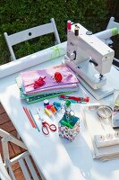 A sewing machine and various sewing utensils on a table outdoors