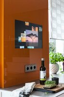 An orange glass panel with an integrated screen in a kitchen