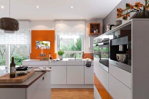 A modern, open-plan kitchen in white with orange accents