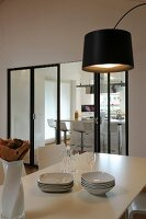 View across dining table and through modern folding doors into kitchen