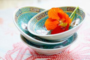 A stack of three oriental bowls decorated with a nasturtium