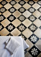 Traditional chequered tiled floor with white flowers on black tiles