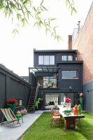 Black house with terraces and colourful, stylish courtyard garden