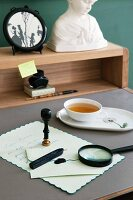 A Biedermeier desk with a letter and seal, an elegant teacup and a framed silhouette