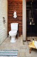 Toilet against rustic wooden wall next to open shower area