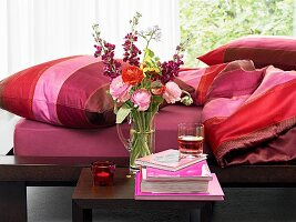 Bedroom with flowers on bedside table and red accents