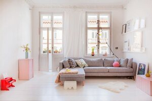 Grey corner sofa and pink cabinets in living area of period apartment